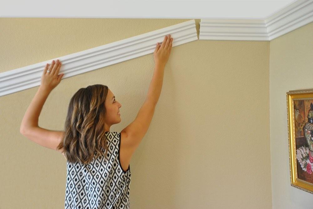 Девушка устанавливает потолочный плинтус